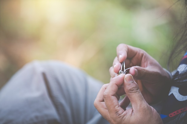 Homem sentado para cortar as unhas.
