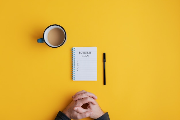 Homem sentado pelo caderno espiral com idéias de plano de negócios prontas para serem escritas nele