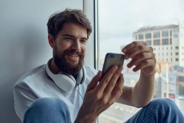 Homem sentado perto da janela em fones de ouvido, ouvindo música em fones de ouvido