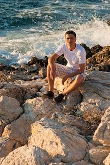 Homem sentado perto do mar