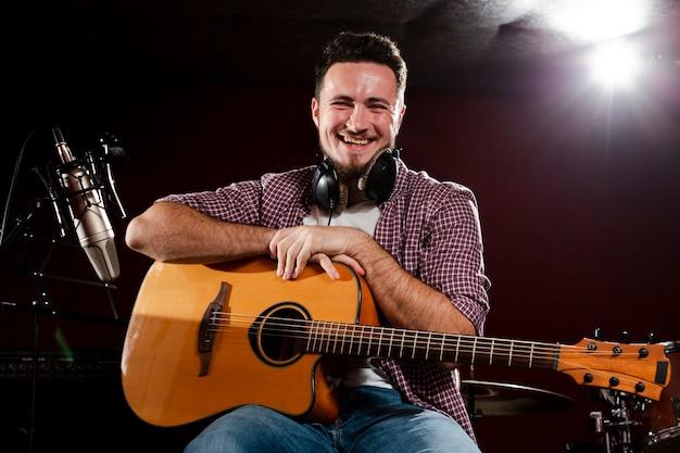Homem sentado, segurando um violão e sorrisos