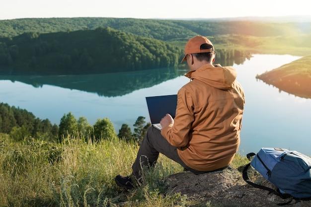 Homem sentado sozinho no deserto da natureza, trabalhando no laptop.
