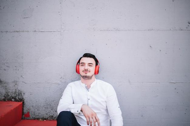 Homem sentado usando fones de ouvido
