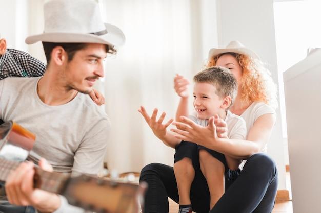 Homem, sentando, com, seu, família, violão jogo