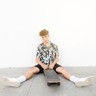 Homem, sentando, com, seu, perna, à parte, sentando, com, skateboard