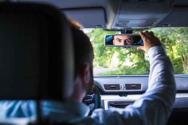 Homem, sentando, dentro, car, ajustar, vista traseira, espelho
