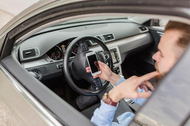 Homem, sentando, dentro, car, usando, móvel, telefone