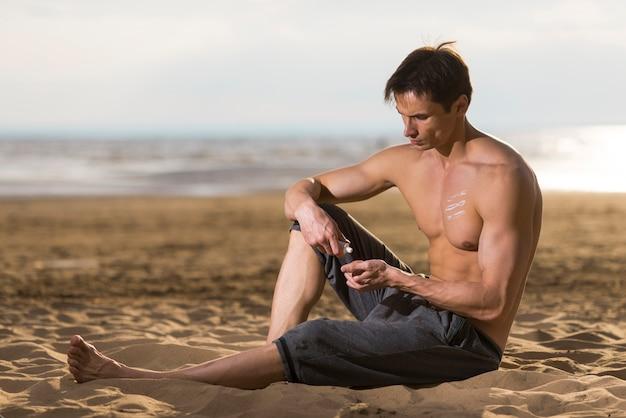 Homem, sentando, e, aplicando, protetor solar, loção