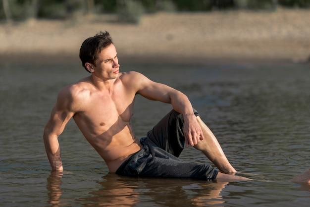 Homem, sentando, em, água, em, praia