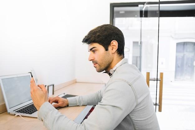 Homem, sentando, em, laptop, usando, smartphone