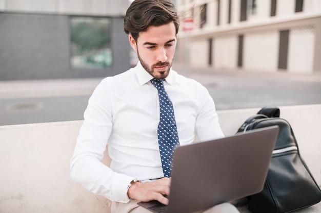 Homem, sentando, ligado, banco, usando computador portátil