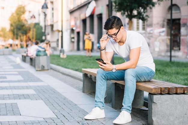 Homem, sentando, ligado, banco, usando, telefone móvel