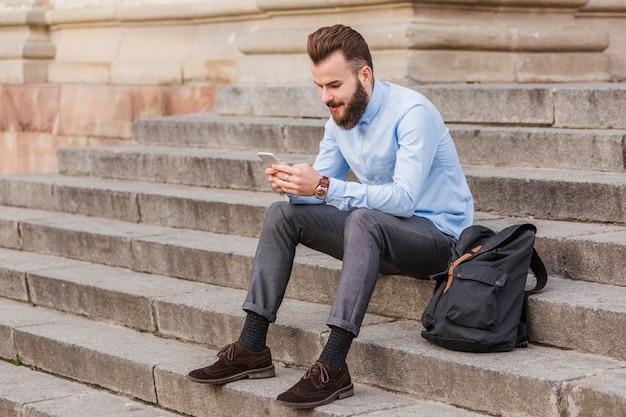 Homem, sentando, ligado, escadaria, usando, cellphone
