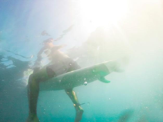 Homem, sentando, ligado, surfboard, em, azul, água