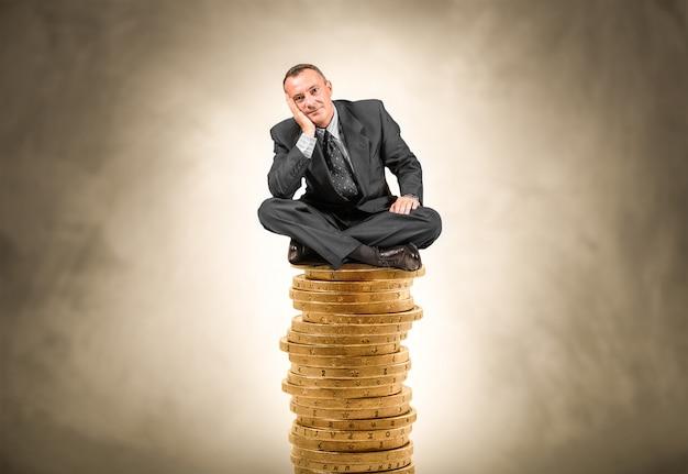 Homem, sentando, ligado, um, pilha moedas