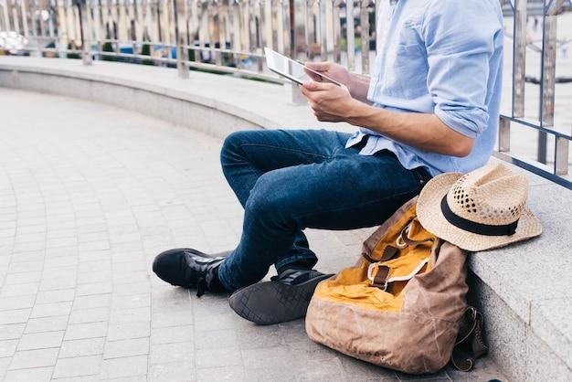 Homem, sentando, perto, trilhos, e, usando, tablete digital, em, ao ar livre