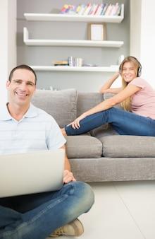 Homem, sentar chão, usando computador portátil, com, mulher, escutar música, ligado, a, sofá, ambos, sorrindo, câmera