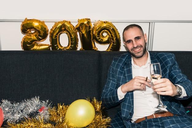 Homem, sentar sofá, com, vidro champanha