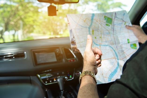 Homem sente-se no carro e segure o mapa com trunfo.