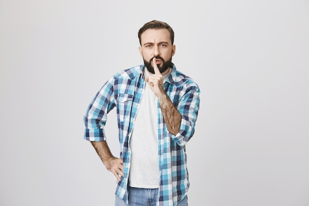 Homem sério barbudo de meia-idade calando-se, faça sinal de silêncio