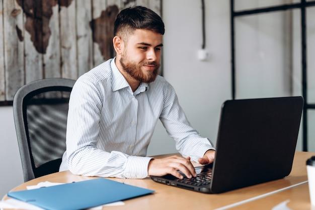 Homem sério, barbudo, trabalhando em um computador no escritório