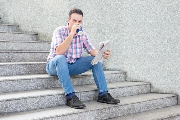 Homem sério bebendo café e lendo jornal