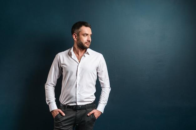 Homem sério bonito em cima de parede azul escuro