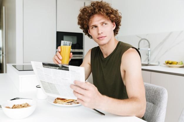 Homem sério bonito segurando jornal e bebendo suco