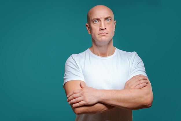 Homem sério careca bonito em t-shirt branca
