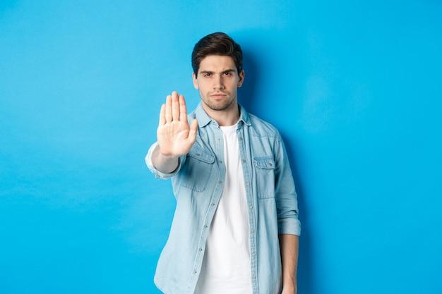 Homem sério, carrancudo e dizendo não, estendendo a mão para a placa de pare a loja, proibindo a ação, em pé contra um fundo azul
