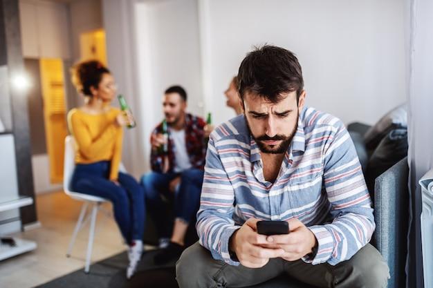 Homem sério caucasiano atraente de camisa listrada, usando telefone inteligente enquanto seus amigos conversando e bebendo no fundo. sala interior.