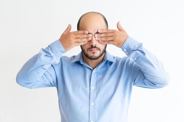 Homem sério, cobrindo os olhos com as duas mãos