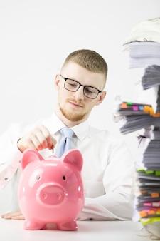 Homem sério colocando moedas no cofrinho rosa no escritório