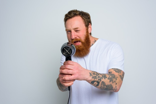 Homem sério com barba brincando com secadores de cabelo e uma arma de fogo