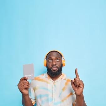 Homem sério com barba espessa apontando para cima e dedo indicador mostrando um espaço em branco contra a parede azul
