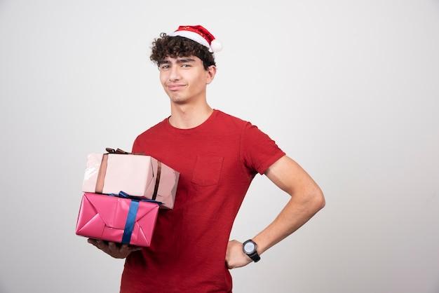Homem sério com chapéu de papai noel segurando presentes