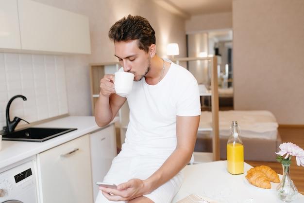 Homem sério com corte de cabelo curto, verificando a correspondência no telefone e bebendo café