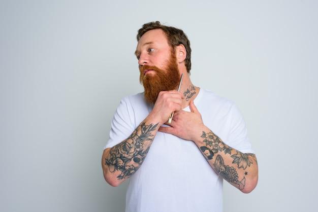 Homem sério com lâmina está focado em cortar sua barba