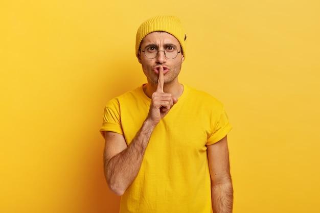 Homem sério com olhar misterioso, mantém o dedo indicador sobre os lábios, olha diretamente para a câmera