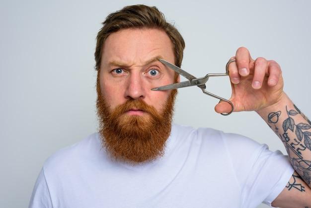 Homem sério com tesoura pronto para cortar a barba
