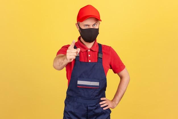 Homem sério com uniforme de trabalhador e máscara protetora mostrando dedo olhando para a câmera