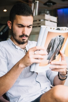 Homem serio concentrado em revista