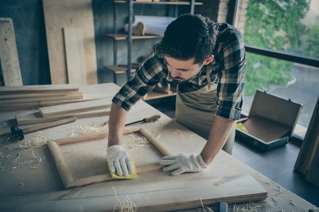 Homem sério, confiante e focado, polindo moldura de madeira tendo acabado de deixar limalha na tela