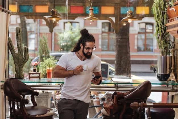 Homem sério confiante segurando uma xícara de café enquanto usa seu smartphone