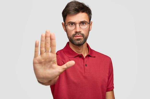 Homem sério de barba preocupado com óculos redondos puxa a palma da mão em direção à câmera, para ou avisa você