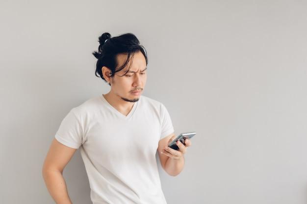 Homem sério de cabelo comprido em camiseta branca casual está usando o smartphone.