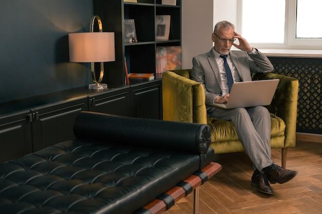 Homem sério de cabelos grisalhos concentrado, sentado em uma poltrona dentro de casa enquanto trabalha em seu laptop