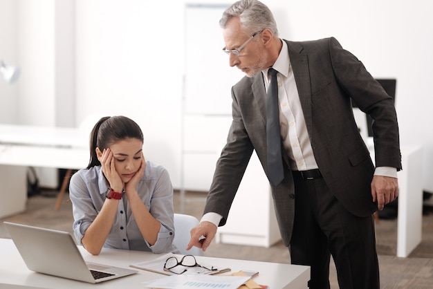 Homem sério de cabelos grisalhos usando fantasia em pé perto de um colega, olhando para baixo