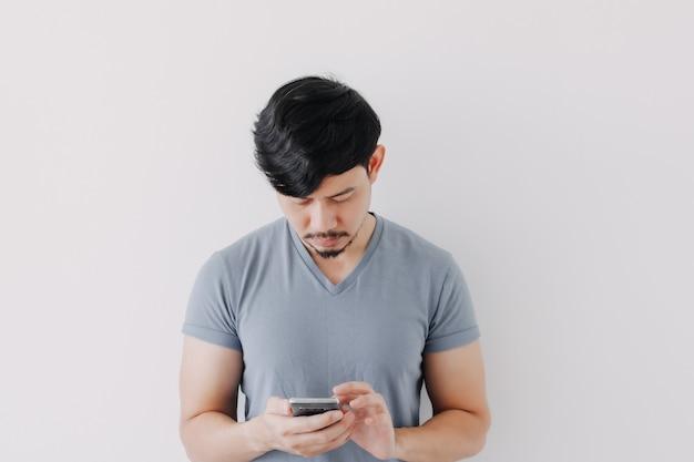 Homem sério de camiseta azul usando smartphone isolado no fundo branco