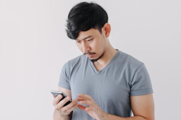 Homem sério de camiseta azul usando um smartphone isolado no fundo branco